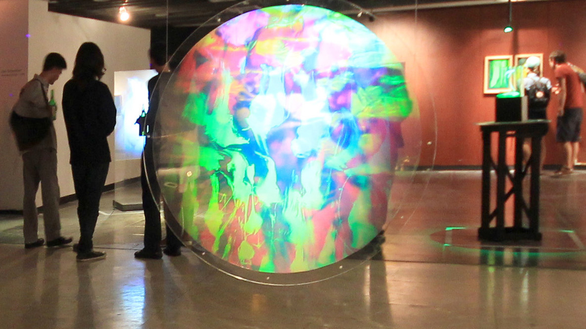 View of the exhibition Interference Coexistence at the HoloCenter Ling Island Cty Clock Tower, circular hologram in front showing abstract field of light by Japanese artist setsuko ishii