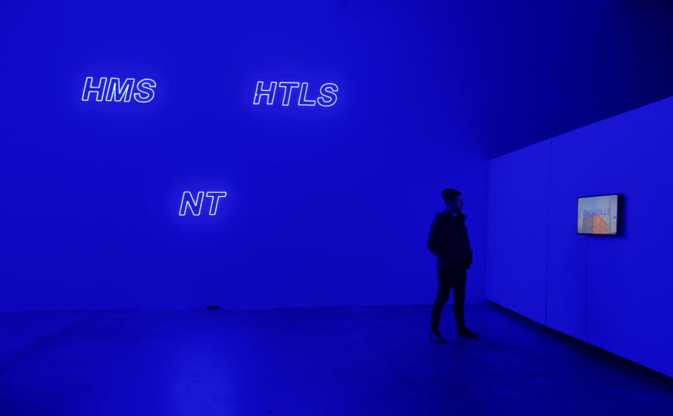 Image shows blue neon letters HMS NT HTLS and person looking at a video screen withe the world BLISSVILE in front of a building