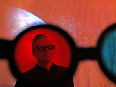 Maximus Clarke photographed infront of his artwork Party of One through anaglyth glasses