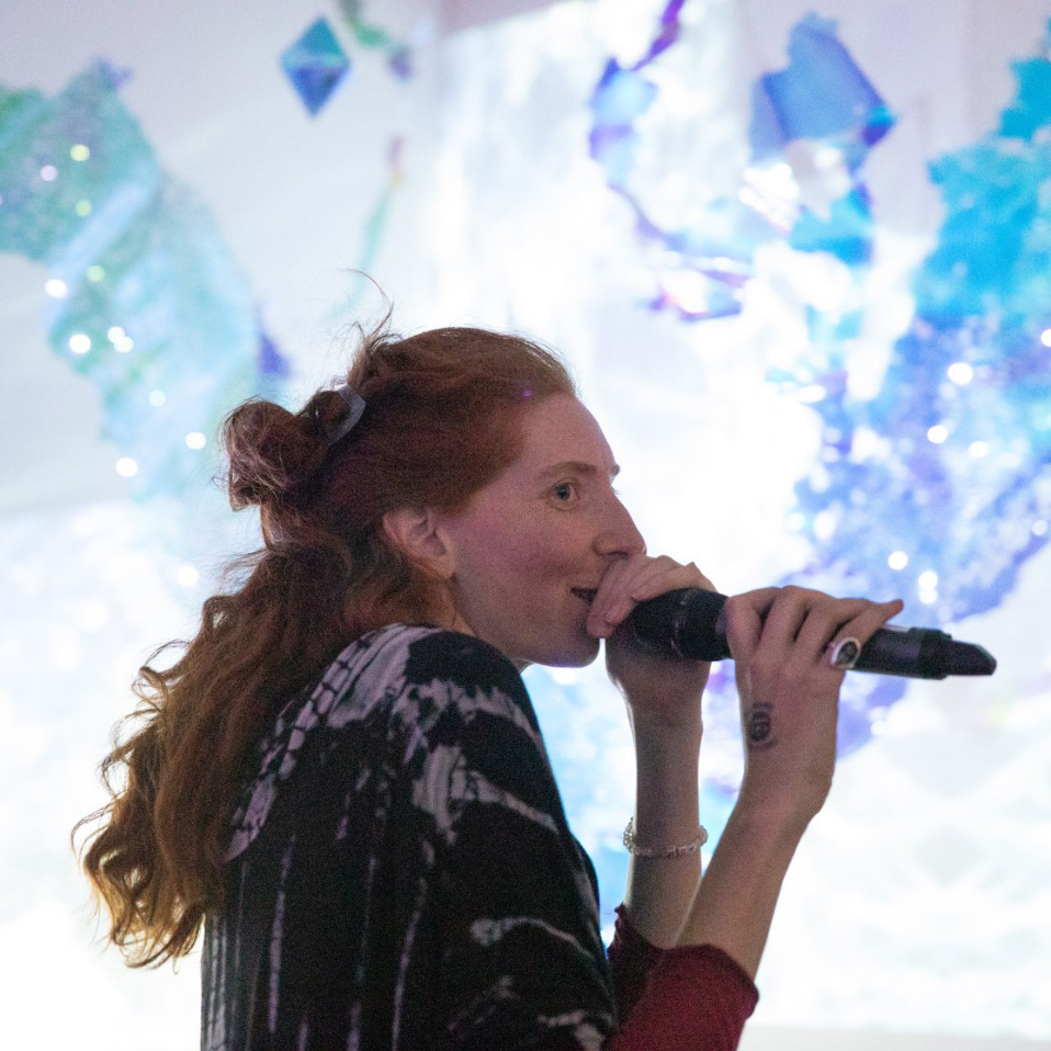 Martina Mrongovius speaking into a microphone at the opening of SPACE:LIGHT. photo by Wen Han-Chan, artwork by Julia Sinelnikova SPACE:LIGHT, 2019